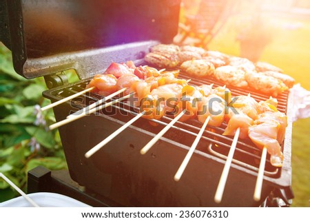 Sizzling burgers and chicken kebabs on hot barbecue outdoor in the evening sun.