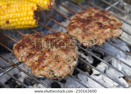 Sizzling Minted Lamb Burgers on Grill with Corn Cobs  - stock photo