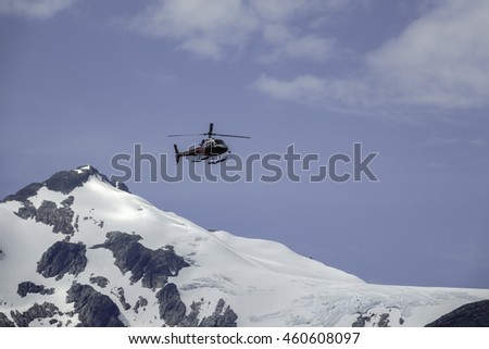 SKAGWAY, ALASKA/USA - JULY 17, 2016: A helicopter flies past a snowy mountain as it returns from an aerial tour of glacial valleys and other rugged terrain in gold-rush country on a summer morning.