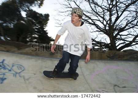 Skate boarder moving along rim of bowl - stock photo