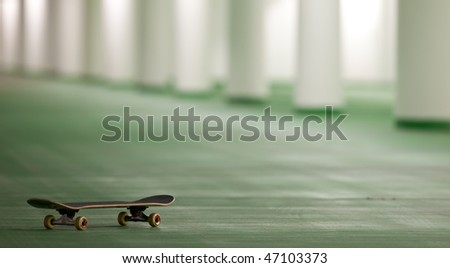 skateboard in an underground parking - perfect place for a ride (color toned image) - stock photo