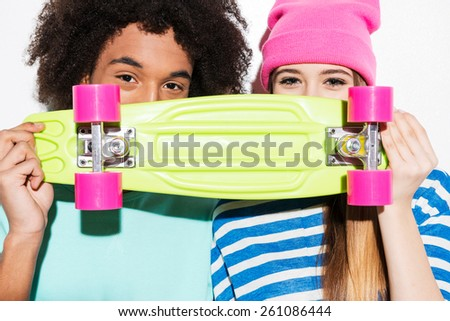 Skateboard lovers. Funky young couple holding skateboard in front of their faces while standing against white background - stock photo