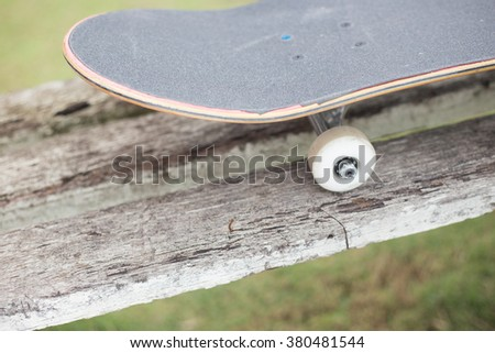 Skateboard on old wood bench - stock photo