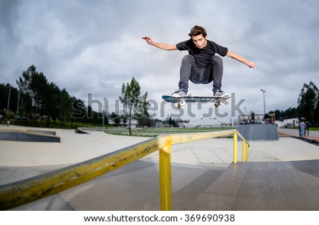Skateboarder doing a ollie over the rail at the skate park.