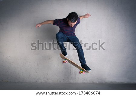 Skateboarder doing a skateboard trick - ollie - against concrete wall. - stock photo
