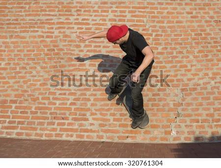 Skateboarder doing a skateboard trick on brick wall - stock photo
