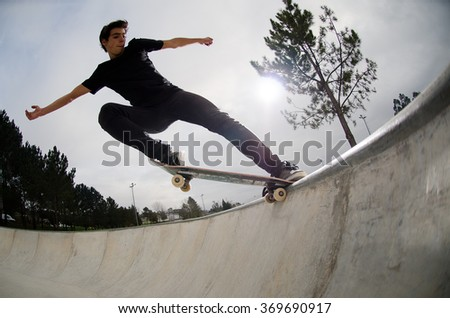 Skateboarder doing a tail slide on a croncrete pool at the skate park.