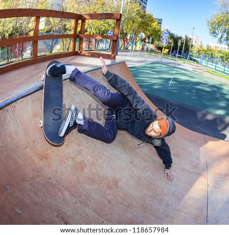 Skateboarder doing masterly lunge in halfpipe - stock photo