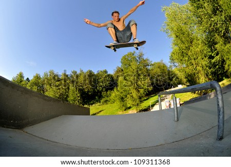 skateboarder flying high at the skate park in summertime.