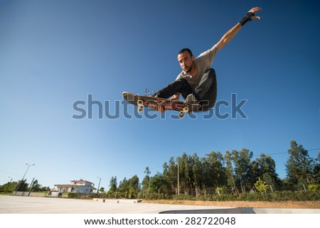 Skateboarder flying over a ramp on blue clear sky. - stock photo