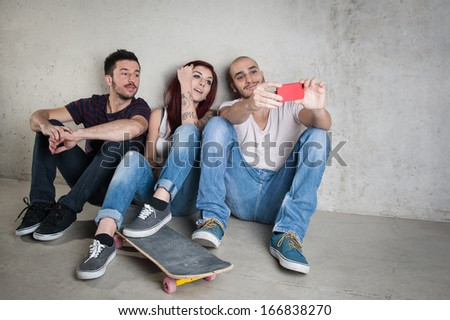 Skateboarder friends taking photo portrait with mobile phone against concrete wall. - stock photo