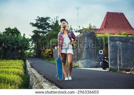 Skateboarder girl stay on the road in cap and checkered shirt with her skateboard, look at the side