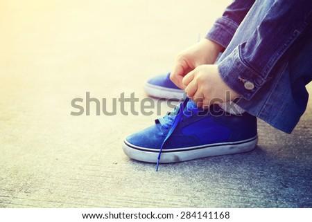 skateboarder hands tying shoelace - stock photo
