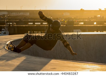 Skateboarder in a concrete pool at skatepark on a beatiful sunset.