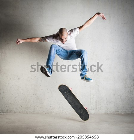 Skateboarder jumping against concrete wall.  - stock photo