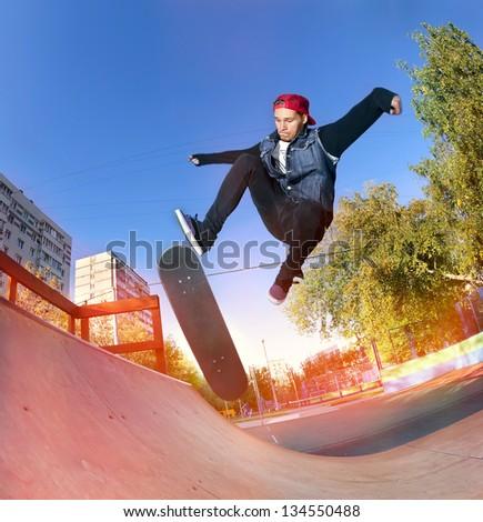 Skateboarder jumping in city skatepark at the halfpipe - stock photo