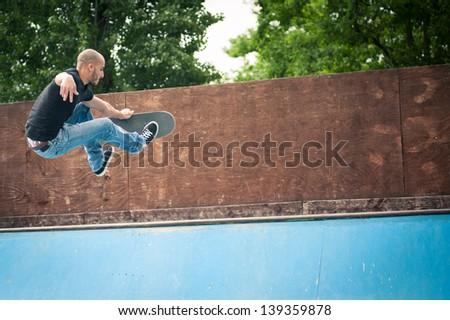Skateboarder jumping in halfpipe at skatepark. - stock photo