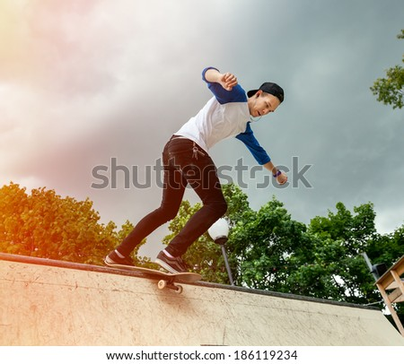 Skateboarder jumping in halfpipe at skatepark on background sky cloudy - stock photo