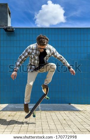 Skateboarder jumping on skateboard - stock photo