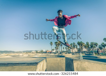 Skateboarder jumping over a gap in a skate park - Young man attempting a trick with his skate  - stock photo