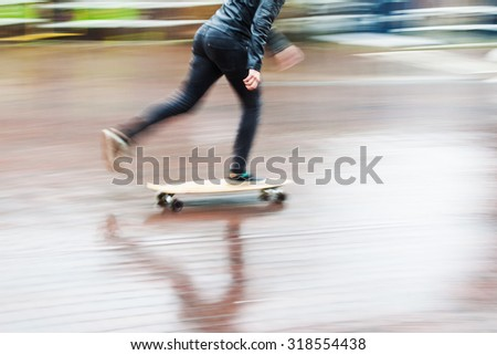 skateboarder on a wet street in motion blur