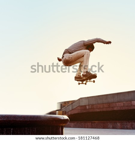 Skateboarder performs a trick in the city on a sunny day - stock photo