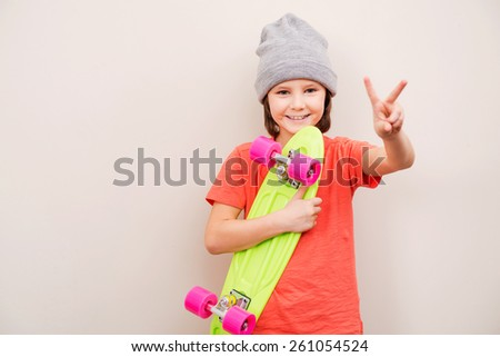 Skateboarding is a way of life. Little boy in hat holding colorful skateboard and smiling while standing against grey background - stock photo