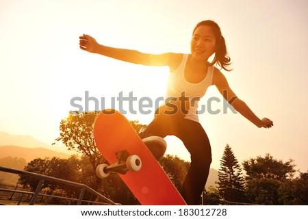 skateboarding woman sunrise - stock photo