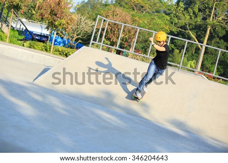 skateboarding young woman riding on a skateboard at skatepark