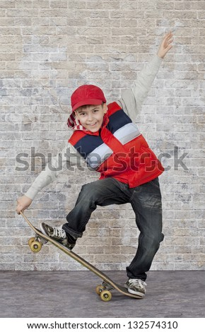 Skater boy crouching on his skateboard in front of brick wall.