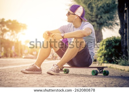skater boy sitting on his longboard and listen to music - stock photo