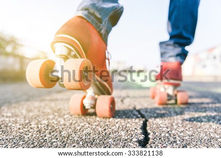 Skater close up in action. Roller skates shoes with sun beam in the background. - stock photo