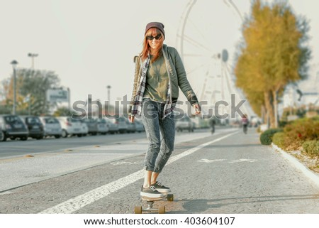 skater girl on the street on a skateboard moving - front view of a fashionable female  skateboarder in her 20's - custom color tones added