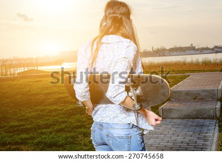 Skater young woman on sunset. Woman with skateboard in her hands outdoors looking at sunset, copyspace. - stock photo