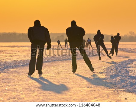 Skaters on a dutch lake seen on their back during the eleven cities tour - stock photo