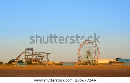 SKEGNESS, ENGLAND - JUNE 8: Skegness beach, the big wheel and the fair ground, early morning, in June. In Skegness, Lincolnshire, England on 8th June 2015.