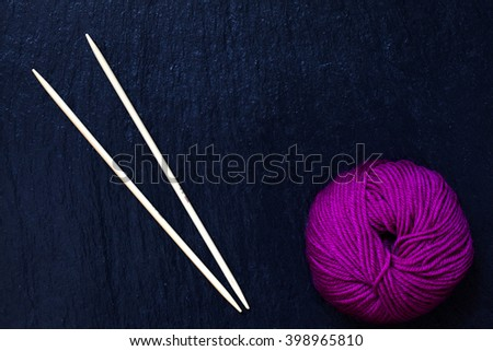 skein of pink yarn with bamboo knitting needles with black slate background