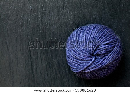 skein of purple yarn with black slate background
