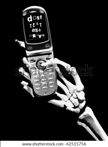 skeletal hand holds a cell phone - the screen reads Don't text and drive - stock photo