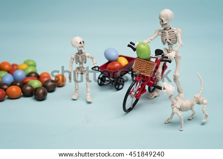 Skeleton and his kid getting chocolate candy - stock photo