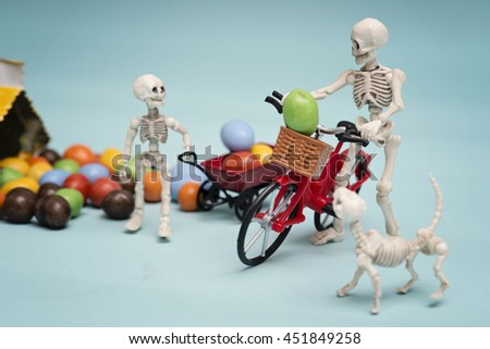 Skeleton and his skeleton kid getting chocolate candy - stock photo