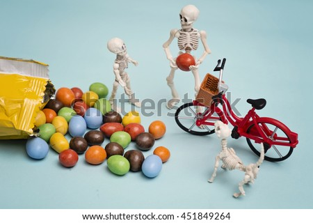 Skeleton and his skeleton kid getting chocolate candy with bicycle - stock photo