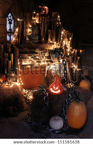 Skeleton and pumpkins in a dark setting for Halloween - stock photo