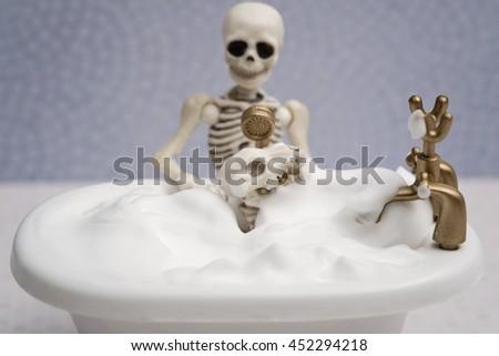 Skeleton bathing his skeleton dog - stock photo