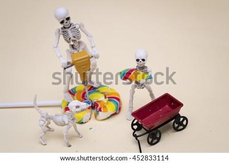 Skeleton breaking lollipop into pieces for the skeleton kid - stock photo