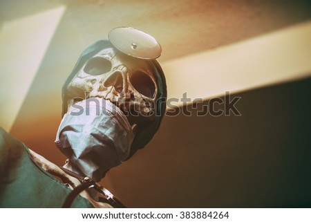 Skeleton Doctor In Surgery. A skeleton in doctor scrubs, hospital attire and classic accessories looking down at you. Edited with vintage film effects. - stock photo
