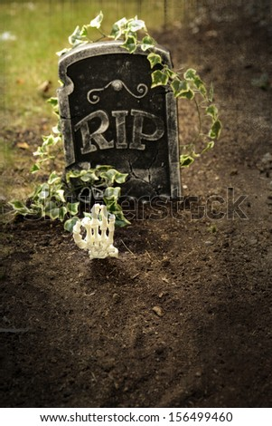 Skeleton hand coming out of grave focus on hand shallow DOF  - stock photo
