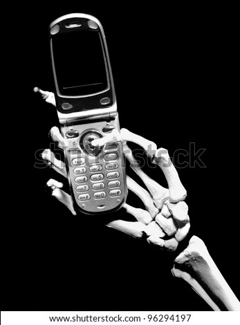 Skeleton hand holding a generic cell phone with a blank screen, isolated on black - stock photo