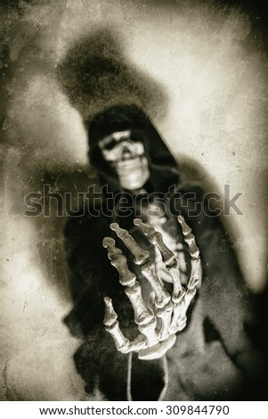 Skeleton Hand Out Vintage. Skeleton in hoodie with hand reaching out as if begging or reaching for viewer. Shot with spot lighting and edited with vintage filters. Skull blurred, hand in focus. - stock photo