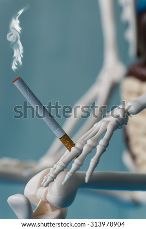 Skeleton hand with cigarette smoking. Hand of death holding a smoking cigarette. Focus on cigarette - stock photo